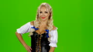 Young sexy oktoberfest woman wearing a traditional bavarian dress dirndl serving beer mugs. Green screen video