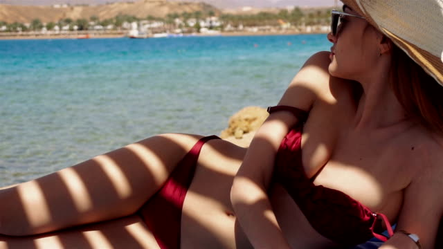 young sexy slim girl in red swimsuit lying on the beach with stripes shadows on her body summer time video