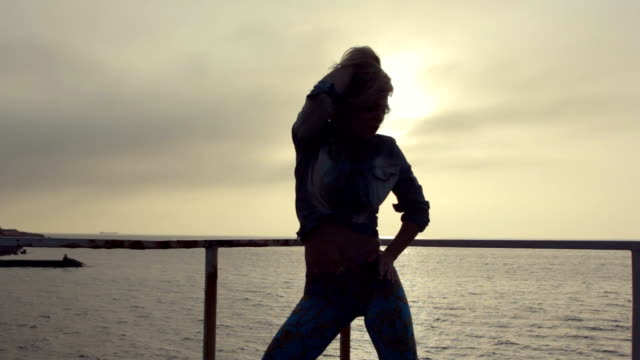 Young sexy woman dancing dancehall on the pier near the sea at a sunset video