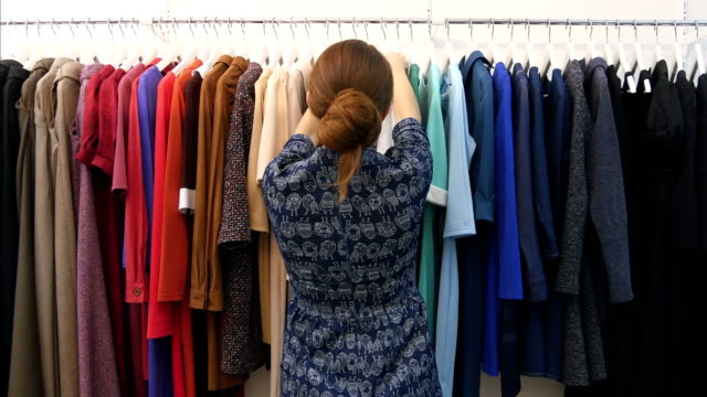 Young shop owner looking at trendy clothes hanged on rail inside the clothes store video