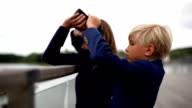 young siblings lookng through binoculars over a balustrade video