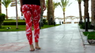 A young slender girl walks slowly among the palm trees along the path to the sea. Brunette with tight buttocks. video