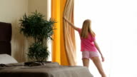 A young slender woman gets out of bed and opening the curtains in the bedroom. video