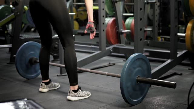 Young slender woman is engaged with a bar in the gym video