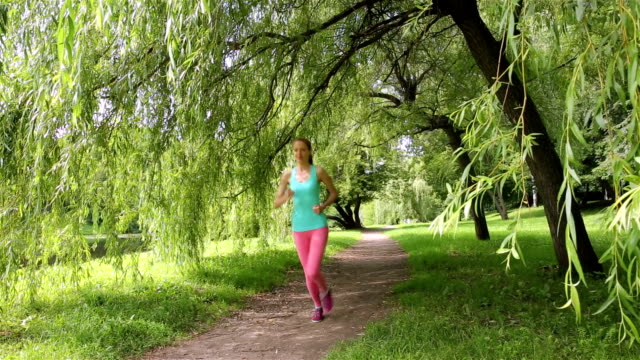 Young slender woman jogging in a city park. Dolly shot. video