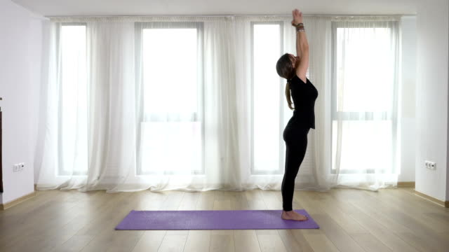 Young slim blonde woman practicing and teaching yoga exercises in studio video
