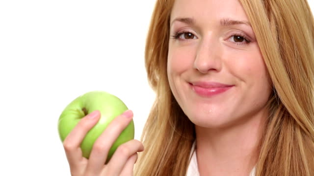 Young slim woman eating juicy green Apple on a white background. video