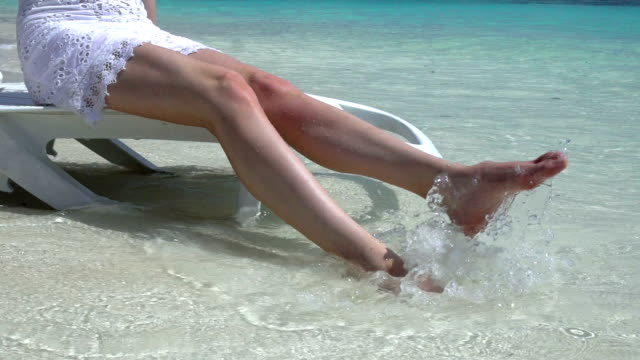 Young slim woman enjoying vacation on a sun lounger on a tropical beach. Slow motion. video