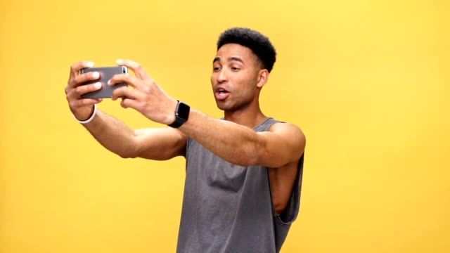 Young smiling african man make selfie over yellow background. video