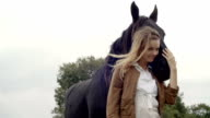 Young smiling blonde woman in nature outdoor hug black horse portrait - slow-motion HD video footage video