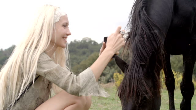 Young smiling blonde woman in nature outdoor take photo with mobile smartphone with black horse - slow-motion HD video footage video