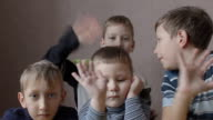 young smiling boys waving their hands video