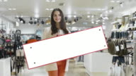 Young smiling brunette woman is holding a blank mock-up sign in a department store. video