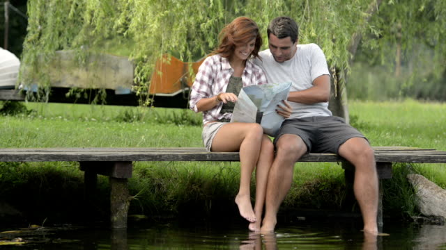 Young smiling couple in nature look at map seated on lake jetty in summer day outdoor - HD video footage video