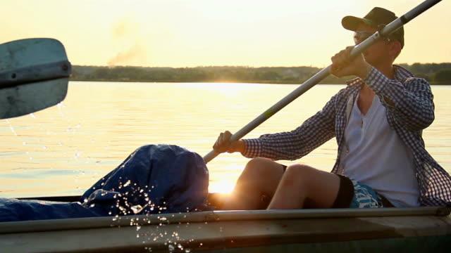 Young smiling man kayaking, enjoying active rest, vacation video