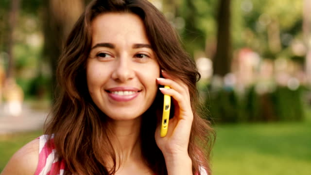 Young smiling pretty woman talking on cell phone against background of summer park video