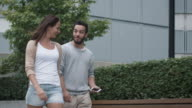 Young Smiling Woman And Man are Walking and Talking in Urban Environment. video