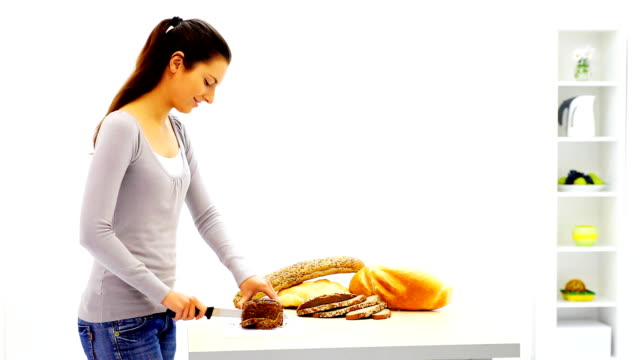 Young smiling woman cutting bread. video