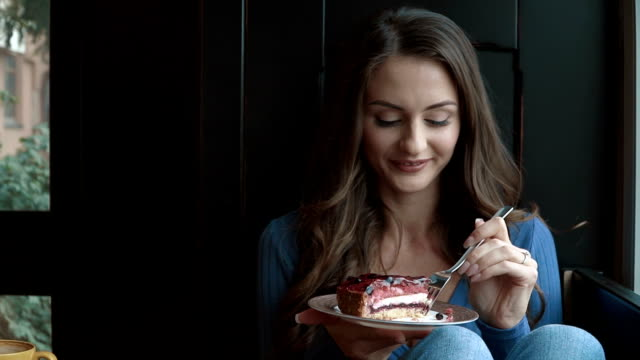Young smiling woman eating pie video