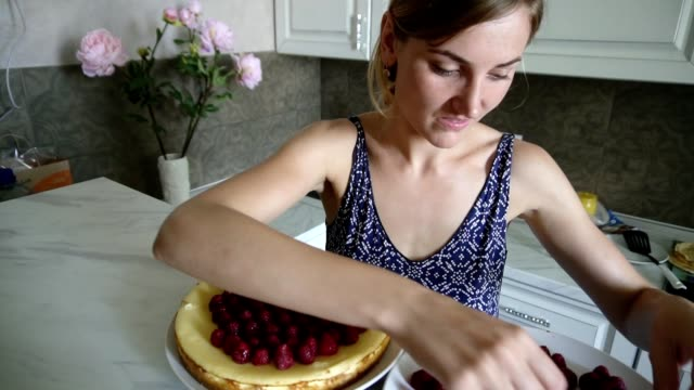 Young smiling woman is adoring and decorating the top of the cake with raspberries in the kitchen at home. Cheese cake decorated with raspberries. Homemade bakery video