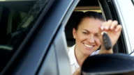 Young smiling woman with keys in a car video