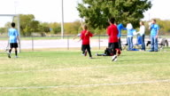 Young soccer team scoring a goal and celebrating video