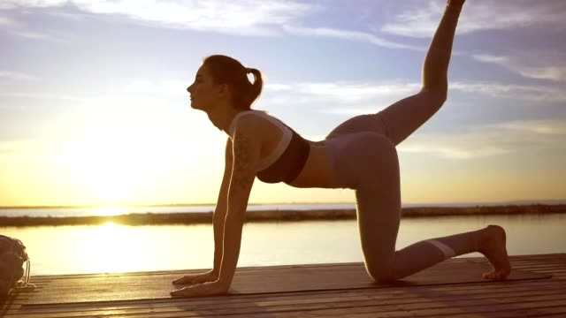 Young sports strong lady at the beach make stretching exercises video