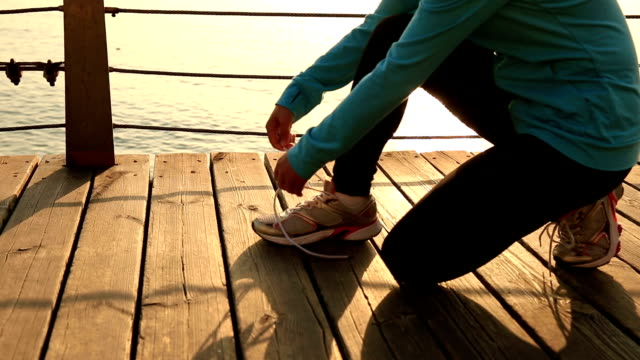 young sports woman runner tying shoelace seaside wooden boardwalk video