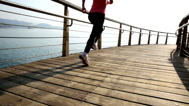 young sports woman running on seaside wooden boardwalk video