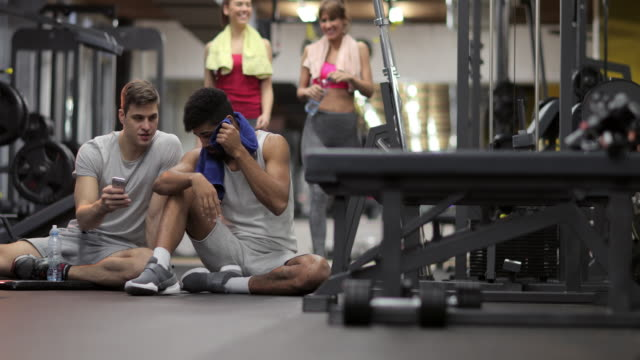 Young sportsmen using cell phone and greeting with two female friends in a gym. video