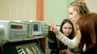 Young student engineers team work in the University of the electrical laboratory. They counsel and test oscilloscope voltmeter readings on the instruments. Future scientists video