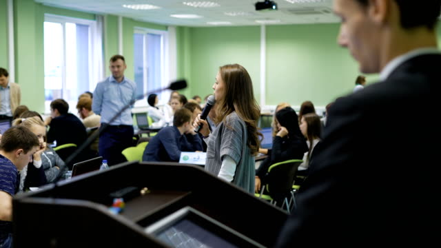 Young student girl with the microphone in her hands speaking to the audience about up-to-date techniques and modern technologies of education. Man in the foreground standing at the desk for speaking video