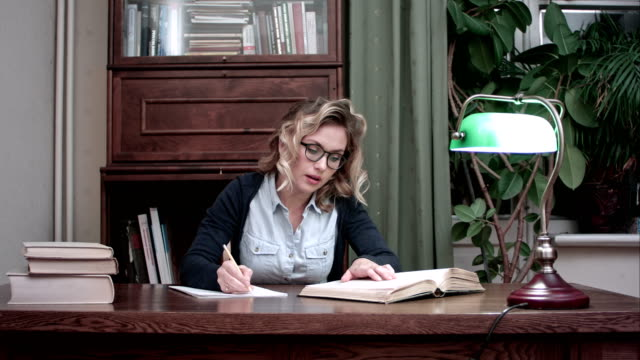 Young student in glasses sitting at a table and writing notes from a book video