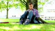 Young student sitting on the grass using tablet pc video