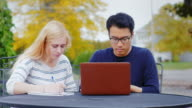 Young students - Asian man and Caucasian woman engaged outdoors. Enjoy a laptop woman takes notes in a notebook video