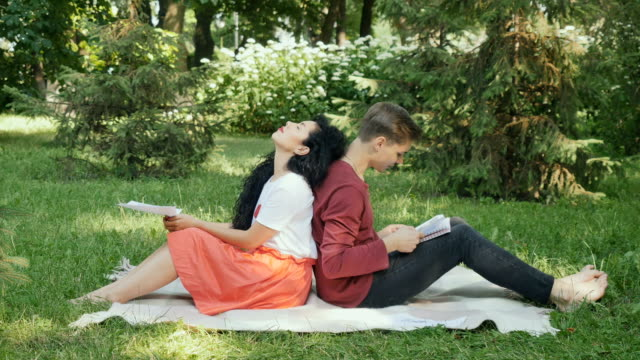 Young students learning educational material in summer park, preparing to exams video