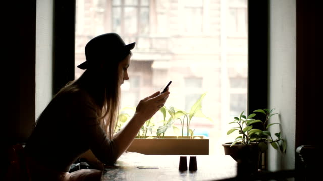 Young stylish woman in hat sitting near the window in cafe and holding the smartphone, using wireless technology video