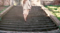 Young stylish woman walking in the city old street, climbing the stairs. Girl spending vacation in Europe video