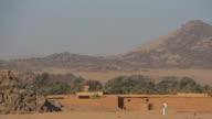 Young Sudanese man walking along settlement in Nubian desert video