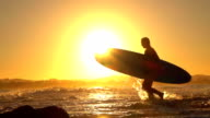 SLOW MOTION: Young surfer girl coming from surfing adventure with surfboard video