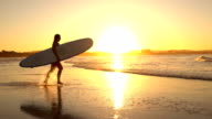SLOW MOTION: Young surfer girl running into ocean splashing water at sunset video
