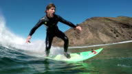 SLOW MOTION UNDERWATER: Young surfer guy riding big wave video