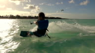 SLOW MOTION: Young surfer man kitesurfing in beautiful turquoise ocean at sunset video