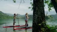 SLOW MOTION: Young surfing couple stand up paddling on lake video