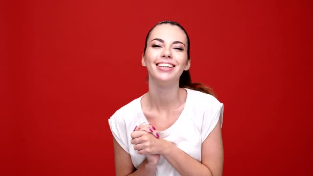 Young surprised caucasian woman smiling over red background. video