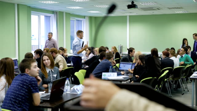 Young teacher in blue shirt with the microphone in his hands explaining rules and task of business gaming simulation to his students in classroom at the university video