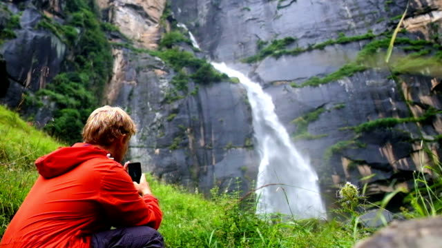 Young teen boy shooting famous Jogini waterfall with his smartphone in Manali, India video