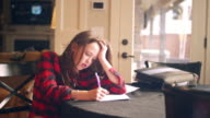 Young teen doing homework at the kitchen table and asking for help video