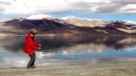 Young teen stone skipping on Tso Moriri lake with the mountain background, Ladakh,India video