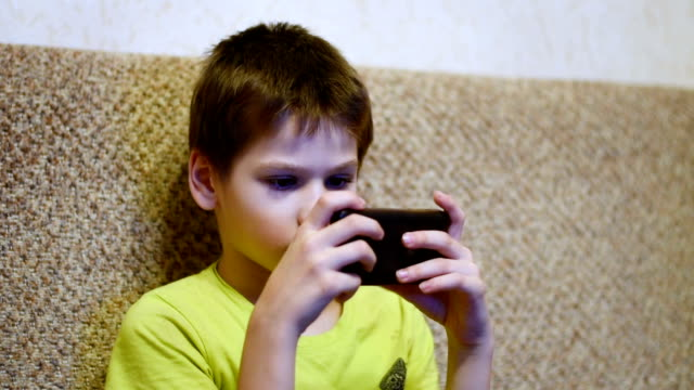 Young teenager playing game on smartphone in home video